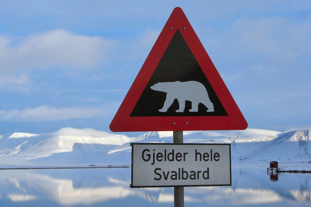 """Špicberky: Známá značka """"Bacha na lední medvědy"""". Dodatková tabule říká: """"Platí po celém Svalbardu."""""""