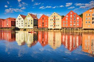 Trondheim, Norsko: Typické barevné dřevěnné domky na Bakklandet zrcadlící se v řece Nidelva